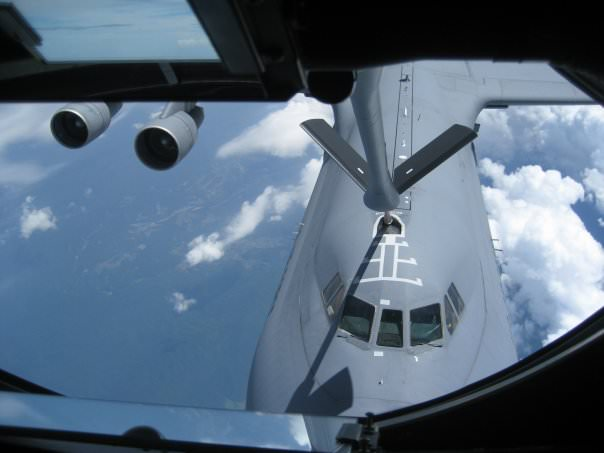 Lisa Mangiafico laying with the boom operator in his station during the refueling of a C-5 Galaxy Military transport aircraft in mid-air.
